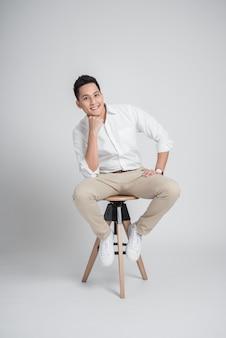 Szczęśliwy ufny azjatycki mężczyzna relaksuje podczas gdy siedzący na krześle