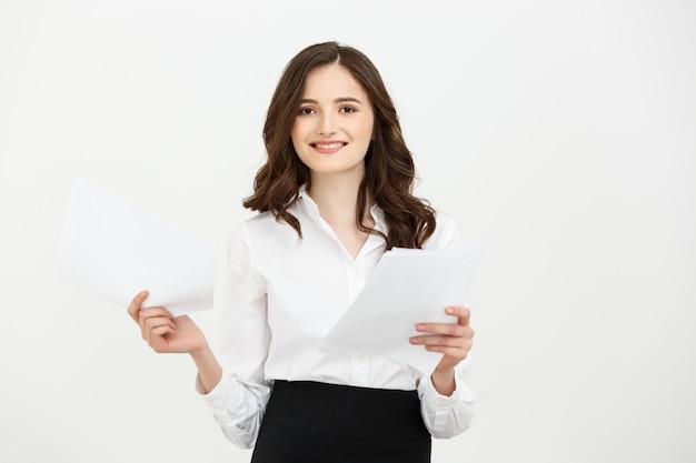 Szczęśliwy ufny młody caucasian kobiety mienia raportu papier stoi ono uśmiecha się odizolowywam nad białym pracownianym tłem.