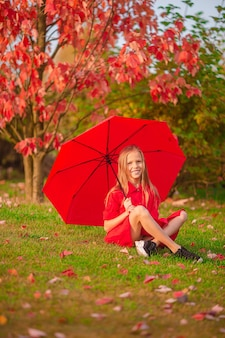 Szczęśliwy uroczy dzieciak z czerwonym parasolem w jesienny dzień