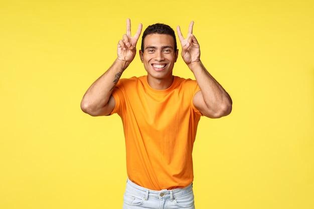 Szczęśliwy, uroczy śliczny latynoski chłopak w pomarańczowej koszulce, pokazujący gest pokoju lub zwycięstwa nad głową