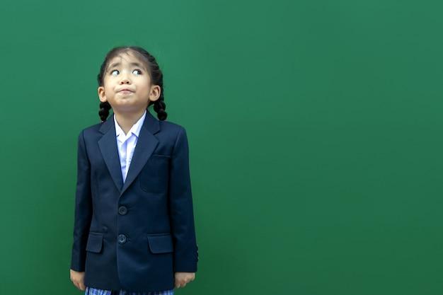 Szczęśliwy uśmiech azjatyckich dzieci w szkole z formalnym mundurem biznesowym na zielonym tle