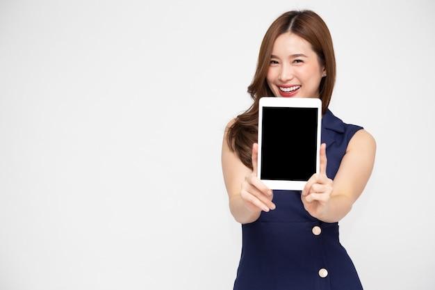 Szczęśliwy uśmiech azjatyckiej kobiety i pokazuje pusty tablet z czarnym ekranem na białym tle nad białym tle
