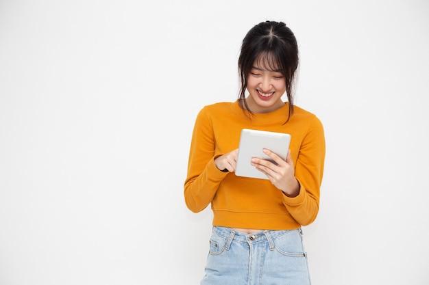 Szczęśliwy uśmiech azjatyckiej kobiety i trzymając tablet na białym tle na białej ścianie