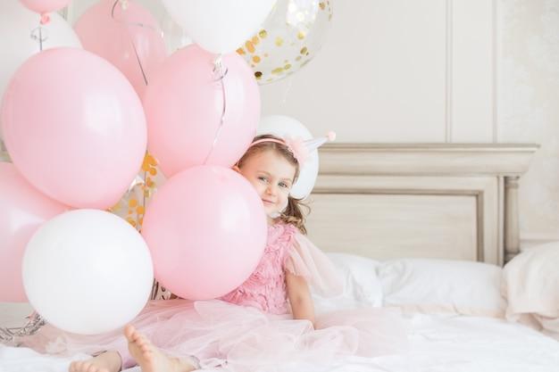 Szczęśliwy uśmiech dziecko dziewczynka na gołych obcasach trzyma pęk balonów dzieci urodziny kopia przestrzeń makieta