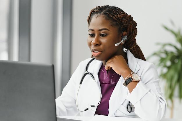 Szczęśliwy uśmiechający się african american kobieta lekarz lub pielęgniarka z zestawem słuchawkowym i laptopem o konferencji lub rozmowie wideo