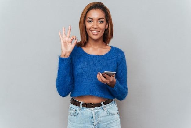 Szczęśliwy uśmiechający się afrykańska kobieta w sweter i dżinsy z telefonem pokazując znak ok. na białym tle szarym tle