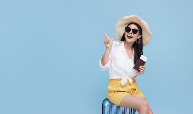 Szczęśliwy uśmiechający się azjatka ubrana w letnie ubrania i kapeluszu z bagażem, ciesząc się letnimi wakacjami i wskazując palcem miejsce na jasnym niebieskim tle.