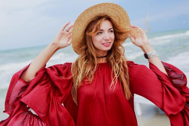 Szczęśliwy uśmiechający się biała imbirowa kobieta w stylowej czerwonej sukience co autoportret telefon komórkowy na plaży w pobliżu oceanu. noszenie słomkowego kapelusza.