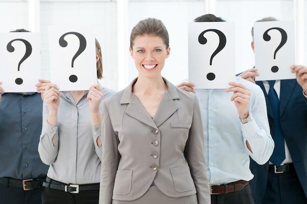 Szczęśliwy uśmiechający się biznes kobieta stojąca z tłumu z innymi ludźmi, ukrywając twarze za znakiem zapytania.