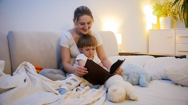 Szczęśliwy uśmiechający się chłopiec maluch słuchanie książki bajki na dobranoc przed pójściem spać.
