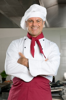 Szczęśliwy uśmiechający się dojrzały szef kuchni patrząc na kamery w swojej kuchni restauracji