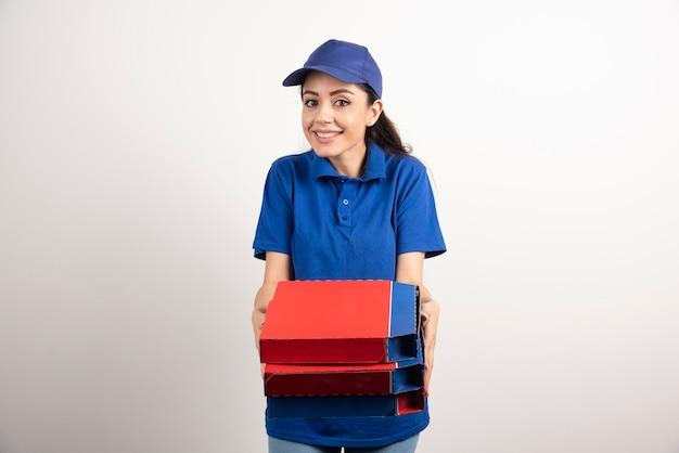 Szczęśliwy uśmiechający się dziewczyna dostawy w niebieskim mundurze z pudełek po pizzy na wynos na białym tle. zdjęcie wysokiej jakości