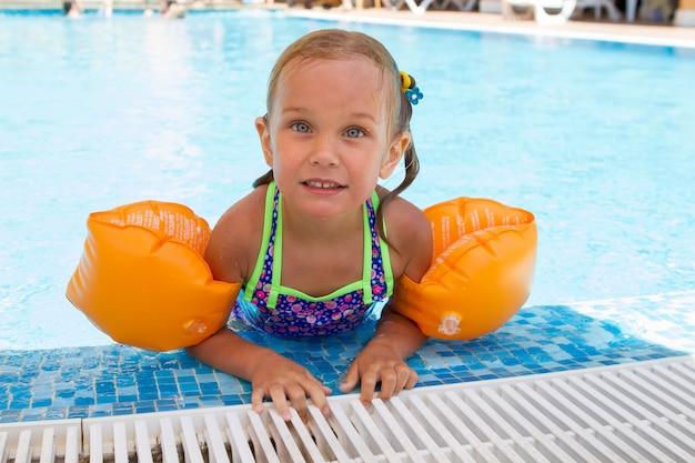 Szczęśliwy uśmiechający się dziewczyna z pływa w ramionach, zabawy i gry w basenie