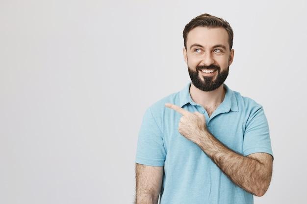 Szczęśliwy uśmiechający się kaukaski facet z brodą, wskazując w lewo