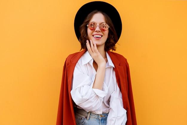 Szczęśliwy uśmiechający się krótkie włosy dziewczyna pozuje na żółtej ścianie. ciepłe kolory. pozytywny nastrój.