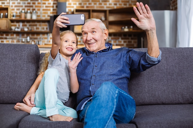 Szczęśliwy uśmiechający się mała dziewczynka siedzi na kanapie z dziadkiem podczas robienia selfie