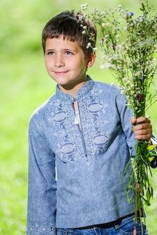 Szczęśliwy uśmiechający się mały chłopiec ubrany w strój narodowy ukraiński styl.