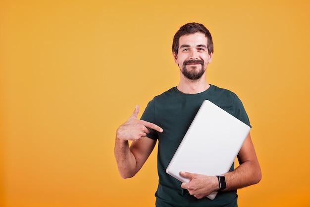 Szczęśliwy uśmiechający się młody człowiek g wskazując na latop, który trzyma w rękach na żółto pomarańczowym tle. połączenie z internetem i promocja