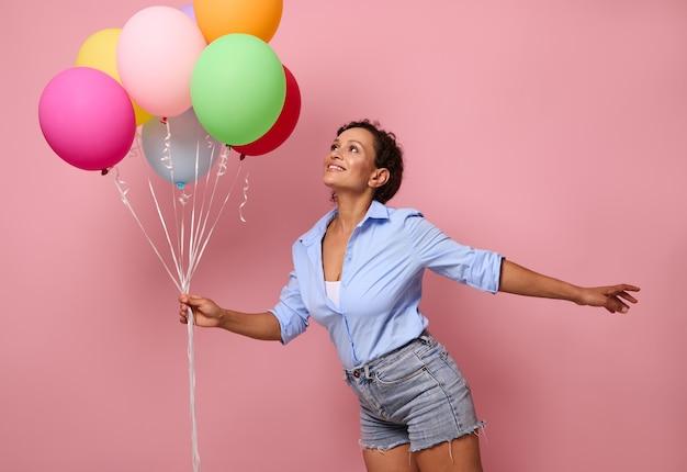 Szczęśliwy uśmiechający się młody rasy mieszanej african american kobieta z bukietem kolorowych tęczowych balonów patrząc w górę i bawiąc się, ubrana w dżinsowe szorty i niebieską koszulę na różowym tle ściany z kopią przestrzeni