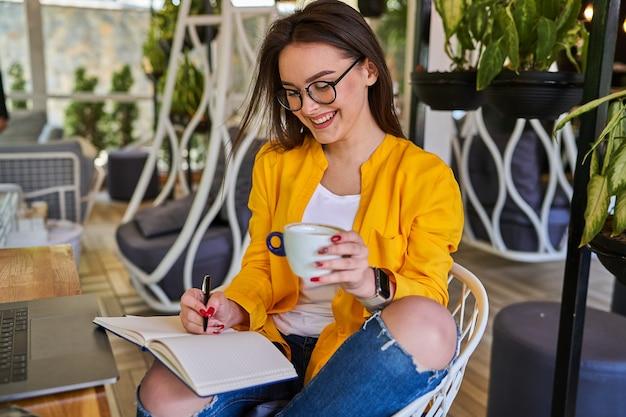 Szczęśliwy uśmiechający się piękna kobieta siedzi i pije kawę z notatnikiem.