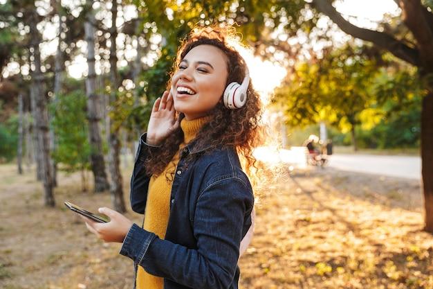 Szczęśliwy uśmiechający się piękna młoda kędzierzawa kobieta spaceru w parku na zewnątrz słuchania muzyki w słuchawkach przy użyciu telefonu komórkowego.