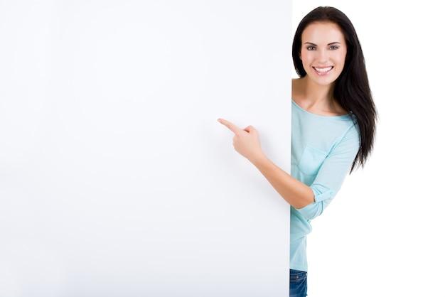 Szczęśliwy uśmiechający się piękna młoda kobieta pokazuje pusty szyld na białym tle