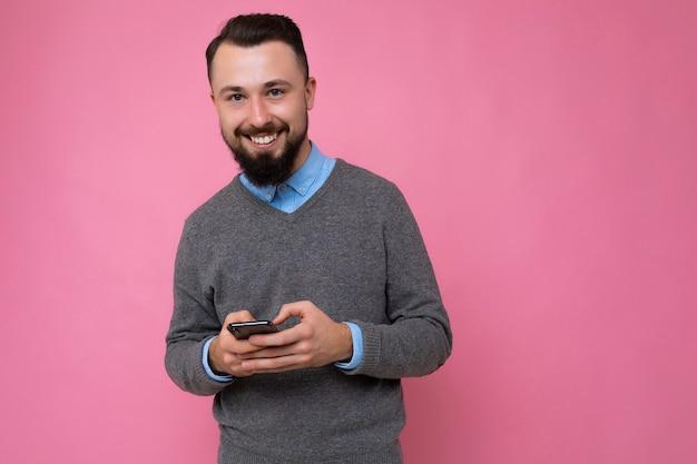 Szczęśliwy uśmiechający się przystojny przystojny brunet brodaty młody człowiek ubrany w szary sweter i niebieską koszulę