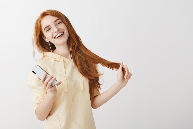 Szczęśliwy uśmiechający się rude dziewczyny słuchanie muzyki w słuchawkach i trzymając telefon komórkowy