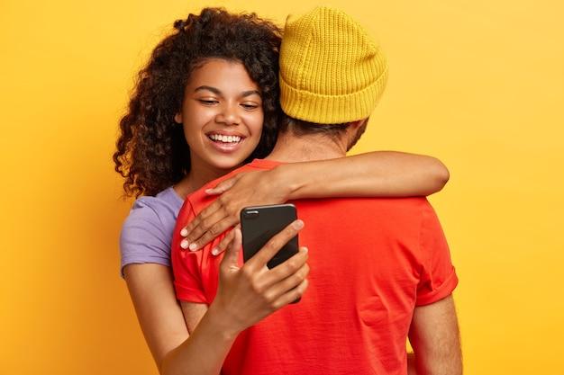 Szczęśliwy uśmiechnięta afro american kobieta obejmuje chłopaka, który stoi z powrotem w aparacie, trzyma telefon komórkowy