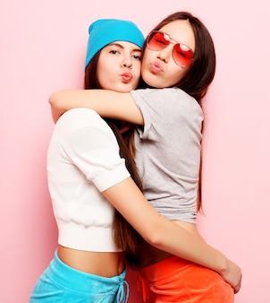 Szczęśliwy uśmiechnięte ładne nastolatki lub przyjaciele przytulanie na różowo
