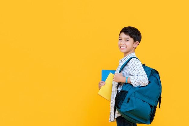 Szczęśliwy uśmiechnięty 10-letni chłopiec rasy mieszanej z plecakiem i książkami gotowymi do szkoły na białym tle na żółtej ścianie z kopią szpachli