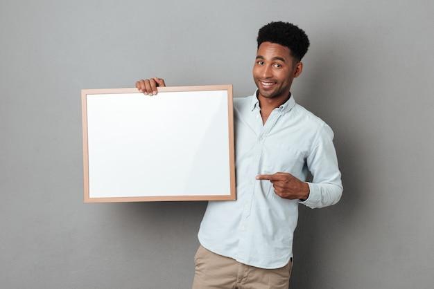 Szczęśliwy uśmiechnięty afrykański mężczyzna wskazuje palec przy puste miejsce deską