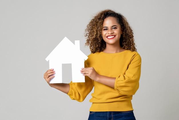 Szczęśliwy uśmiechnięty amerykanin afrykańskiego pochodzenia kobiety mienia papieru dom