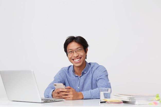 Szczęśliwy uśmiechnięty azjatycki młody biznesmen w okularach za pomocą telefonu komórkowego, śmiejąc się i pracując przy stole z laptopem na białej ścianie