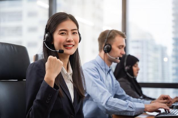 Szczęśliwy uśmiechnięty azjatykci kobiety centrum telefoniczne, operator jest ubranym słuchawki pracuje na komputerze i opowiada z klientem z jej usługowym umysłem