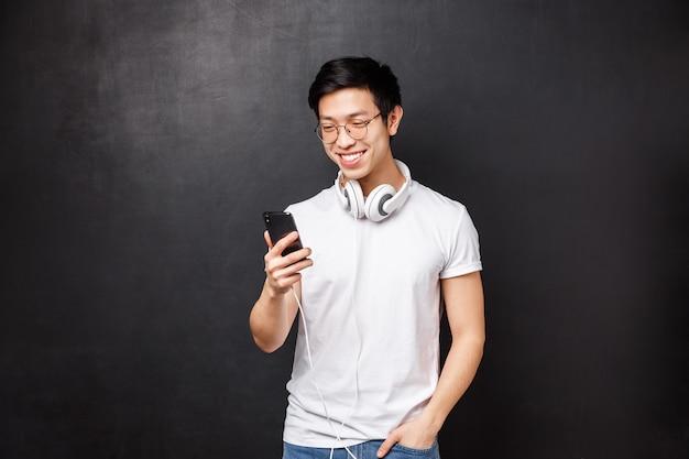 Szczęśliwy uśmiechnięty azjatykci męski uczeń stoi niezobowiązująco w koszulce, jest ubranym hełmofony nad szyją