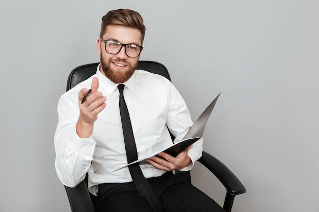 Szczęśliwy uśmiechnięty biznesmen trzyma falcówkę w eyeglasses