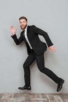 Szczęśliwy uśmiechnięty biznesmen w kostiumu pozuje podczas gdy skaczący