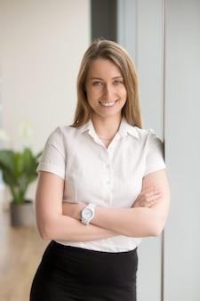 Szczęśliwy uśmiechnięty bizneswoman patrzeje kamerę z rękami krzyżować, portret