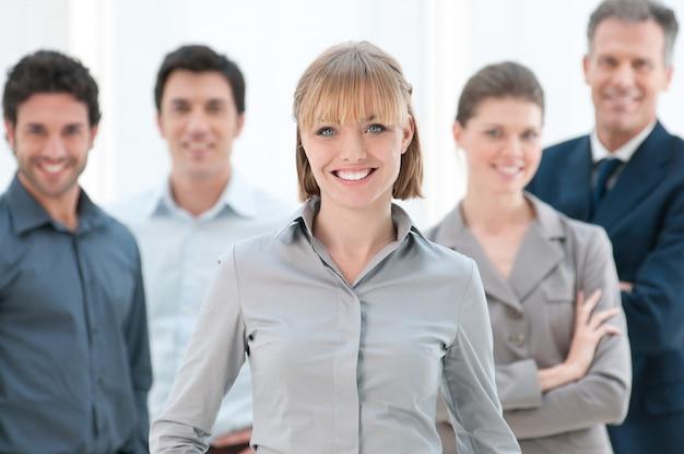 Szczęśliwy uśmiechnięty bizneswoman stojący ze swoimi kolegami w nowoczesnym biurze