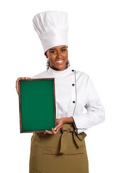 Szczęśliwy uśmiechnięty brazylijski kucharz kobieta na białym tle, trzymając ładną teksturowaną tablicę do reklamy.