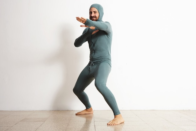 Szczęśliwy uśmiechnięty, brodaty dopasowany mężczyzna ubrany w snowboardowy termiczny strój kąpielowy z wełny merynosów i zachowuje się jak ninja w pozycji obronnej, odizolowany na białym