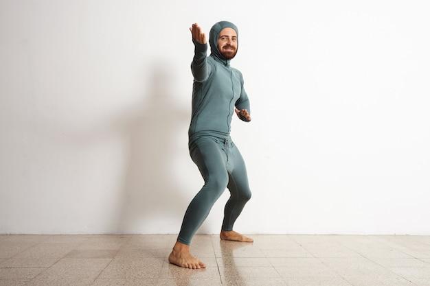 Szczęśliwy uśmiechnięty, brodaty dopasowany mężczyzna ubrany w snowboardowy termiczny strój kąpielowy z wełny merynosów i zachowuje się jak ninja w pozycji powitalnej, odizolowany na białym