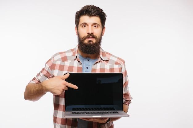 Szczęśliwy uśmiechnięty brodaty mężczyzna trzyma pusty ekran laptopa na białym tle nad białą ścianą