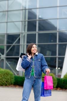 Szczęśliwy uśmiechnięty brunetki kobiety odprowadzenie z barwionymi torba na zakupy na ulicie blisko centrum handlowego. styl życia na zakupy