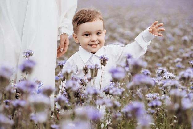 Szczęśliwy uśmiechnięty chłopiec biegnie przez kwitnące pole