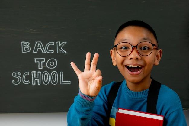Szczęśliwy uśmiechnięty chłopiec idzie do szkoły po raz pierwszy