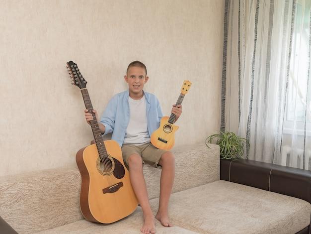 Szczęśliwy uśmiechnięty chłopiec nauka gry na gitarze akustycznej.