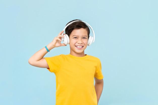 Szczęśliwy uśmiechnięty chłopiec rasy mieszanej słuchania muzyki