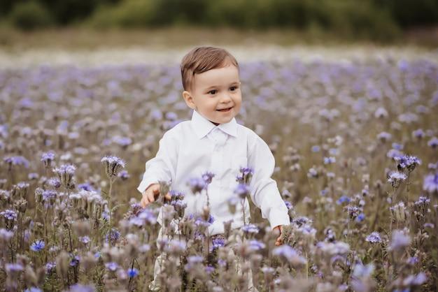 Szczęśliwy uśmiechnięty chłopiec świetnie się bawi w dziedzinie kwiatów